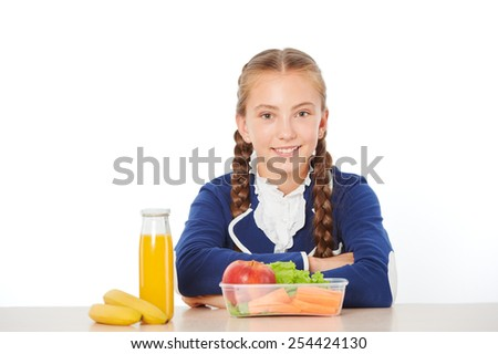 Photo of smiling school girl at lunch. Isolated on white background. Concept for healthy eating at school - stock photo
