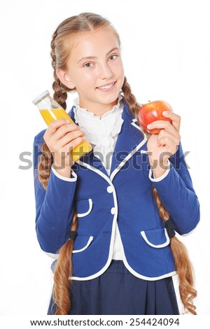 Photo of smiling school girl with juice and apple. Isolated on white background. Concept for healthy eating at school - stock photo
