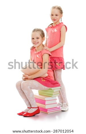 Photo of smiling sisters sitting on a stack of books - stock photo