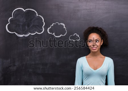 Photo of smiling young afro-american woman on chalkboard background. Woman looking at cloud formed dialog - stock photo