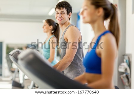 Photo of smiling young people doing workout on a treadmill