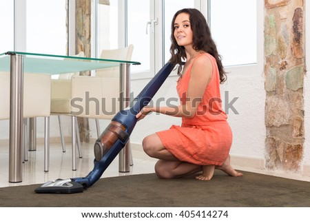 Photo of smiling young woman in dress vacuuming living room