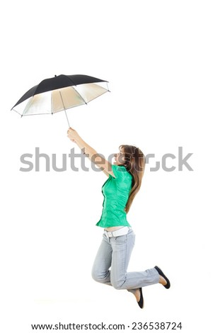 Photo of smiling young woman or girl in green shirt and gray jeans pants with umbrella jumping in air up studio isolated on white . Carefree and serene happiness concept - stock photo