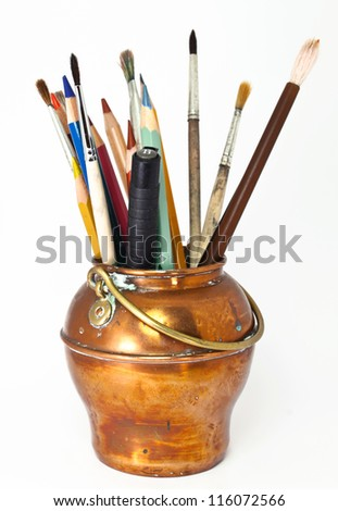 photo of some color pencils and brushes in vintage brass jar