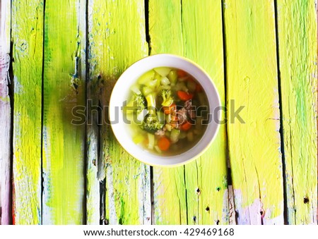 Photo of soup in a plate on green background - stock photo
