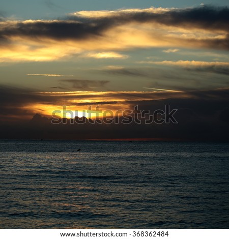 Photo of spectacular marine seashore dark blue sea with ripples against yellow-light illumination of low level cloudy sky at sunset time dusk bleakness over seascape background, square picture - stock photo