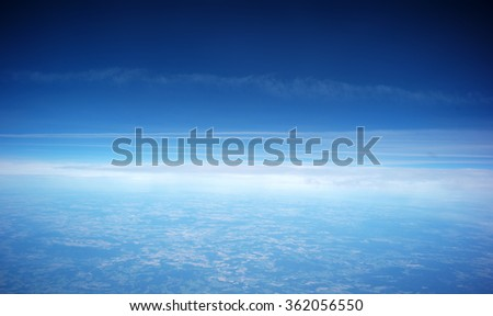 Photo of spectacular skyline view above sea of clouds in blue sky from airplane window over breath-taking tranquil earth background, horizontal picture - stock photo