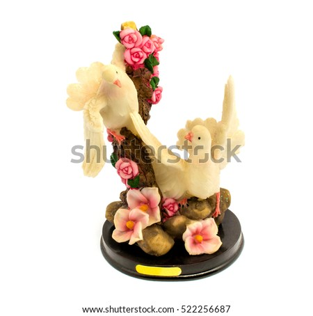 Photo of statuette of porcelain pigeons with flowers isolated on white background
