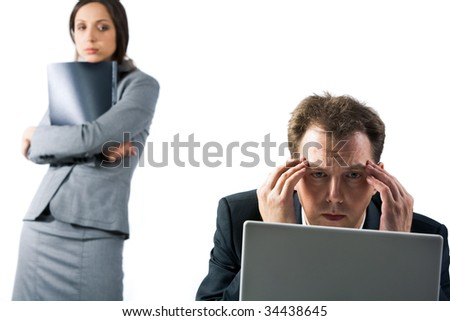 Photo of stressed businessman looking at laptop screen with troubled female at background - stock photo