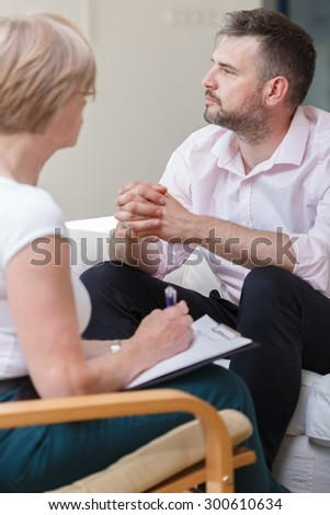 Photo of stressed male during session with female psychiatrist - stock photo