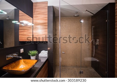 Photo of stylish dark bathroom interior with big shower