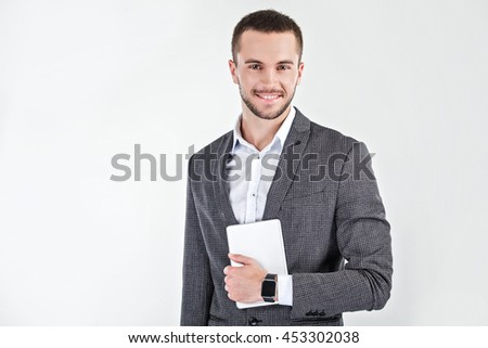 Photo of stylish handsome young man isolated on white background. Man with smart watch holding tablet computer - stock photo