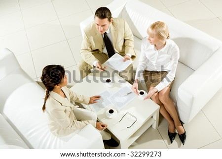 Photo of successful business partners discussing papers and plans at meeting - stock photo