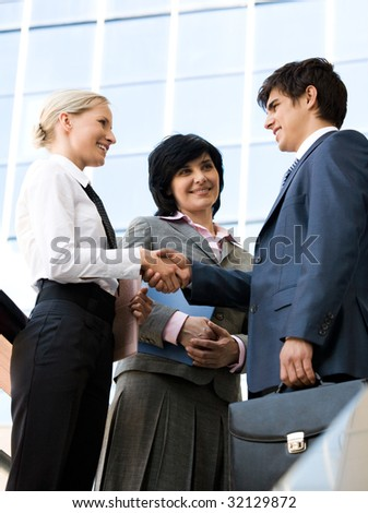 Photo of successful business partners handshaking after signing contract while their colleague looking at them - stock photo