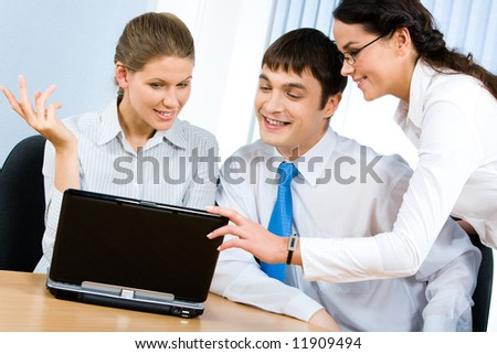 Photo of successful business partners speaking about new working ideas while looking at laptop screen at meeting