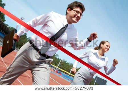 Photo of successful businessman crossing finish line during race - stock photo