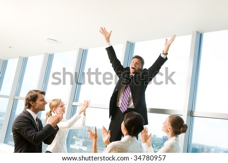 Photo of successful businessman raising his arms and shouting surrounded by his colleagues applauding