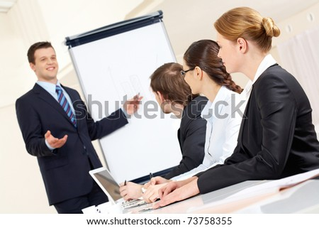 Photo of successful businessman sharing ideas by whiteboard with partners at presentation