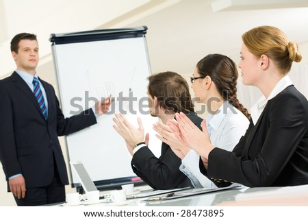 Photo of successful businessman standing by whiteboard while partners applauding to him after presentation