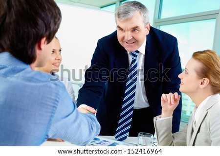 Photo of successful businessmen handshaking after striking deal surrounded by women - stock photo