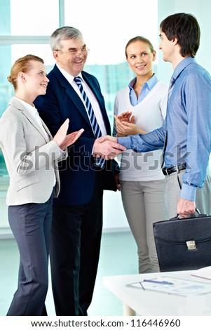 Photo of successful businessmen handshaking after striking deal with applauding women near by - stock photo