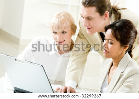 Photo of successful businesspeople looking at laptop display while brainstorming
