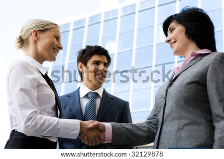 Photo of successful businesswomen handshaking after striking deal while happy man looking at them - stock photo