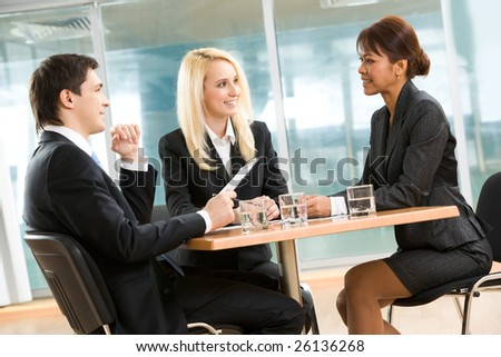 Photo of successful employees gathered around table explaining their ideas in office - stock photo