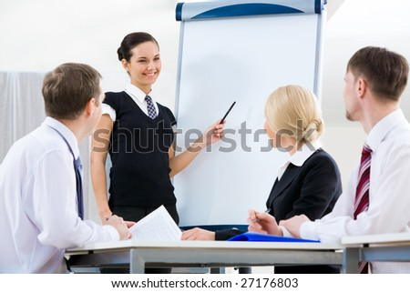 Photo of successful female standing by whiteboard while explaining her idea to colleagues - stock photo