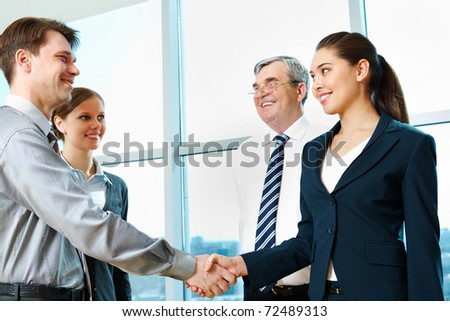 Photo of successful partners handshaking after signing agreement at meeting - stock photo