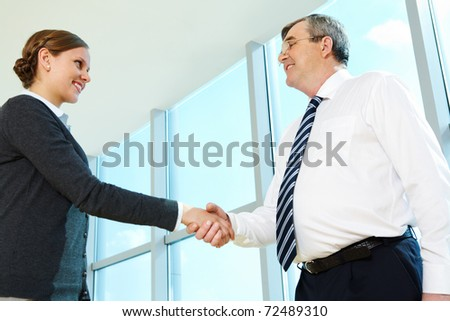 Photo of successful partners handshaking after striking deal