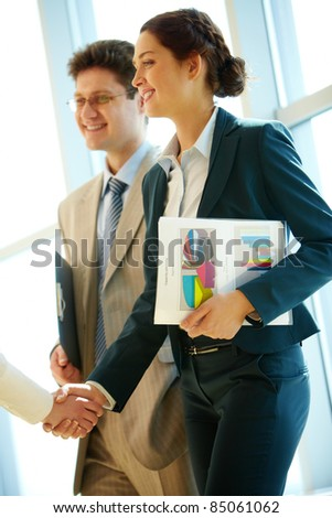 Photo of successful woman handshaking with partner after striking deal at meeting - stock photo