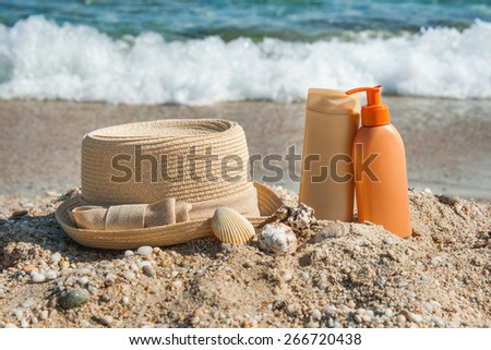 Photo of suntan lotion bottles and hat on the beach.Sun protection - stock photo
