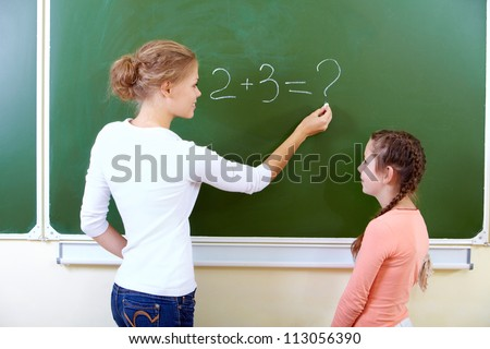Photo of teacher writing sum on blackboard with pretty pupil near by - stock photo