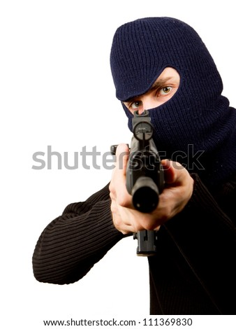 Photo of terrorist with gun attacking someone while pointing it forwards - stock photo