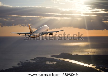 Photo of the aircraft flying over the sea at sunset - stock photo