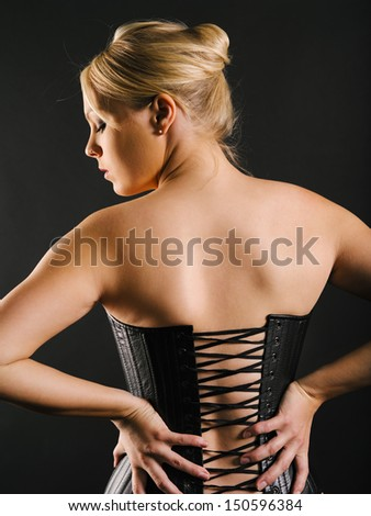 Photo of the back of a beautiful blond woman wearing a leather corset.