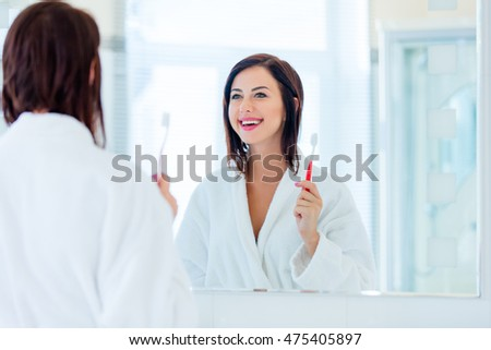 photo of the beautiful young woman looking at herself in the mirror and holding her toothbrush