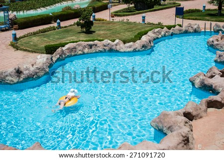 Photo of the beautiful young woman on life preserver in pool