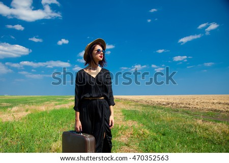 photo of the beautiful young woman with suitcase in the field