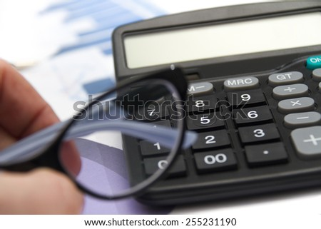 Photo of the Businessman analyzing investment charts with calculator