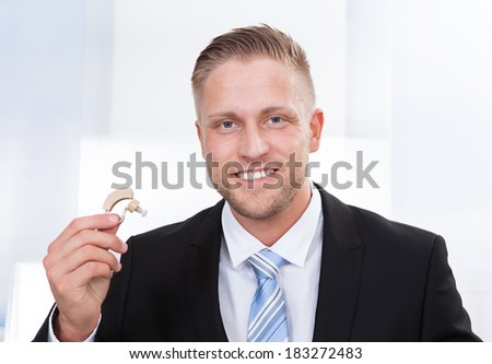 Photo of the businessman holding hearing aid