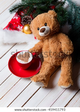 photo of the cup of coffee, teddy bear and christmas decorations on the brown wooden background