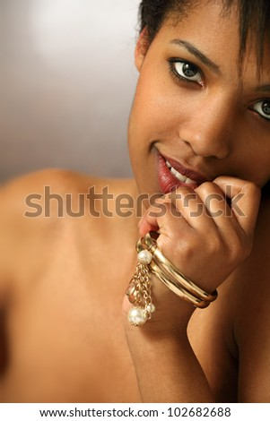 Photo of the face of a beautiful black woman in her twenties. Shallow depth of field, focusing on the eyes. - stock photo