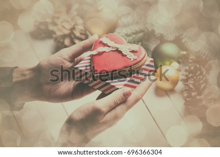 photo of the female hands holding a cookie and gift on the christmas decorations background
