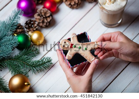 photo of the female hands wrapping a man shaped cookie on the christmas decorations background - stock photo