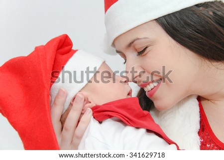 Photo of the Happy mother with male baby wearing christmas hats