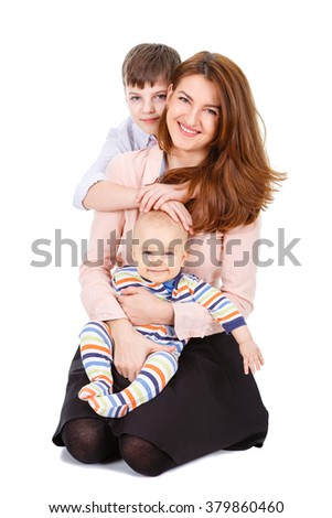 Photo of the happy young mama with little child and infant sitting on the floor - isolated on white background. Concept of young happy family - stock photo