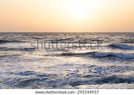 Photo of the sea waves on the background of sunrise or sunset. The sky in a beautiful gold, blue, light blue and orange colors.