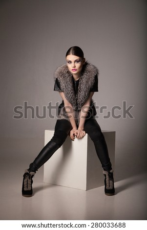 photo of the sexual dark- haired model sitting on the grey cube leaning forward, over gray background. - stock photo